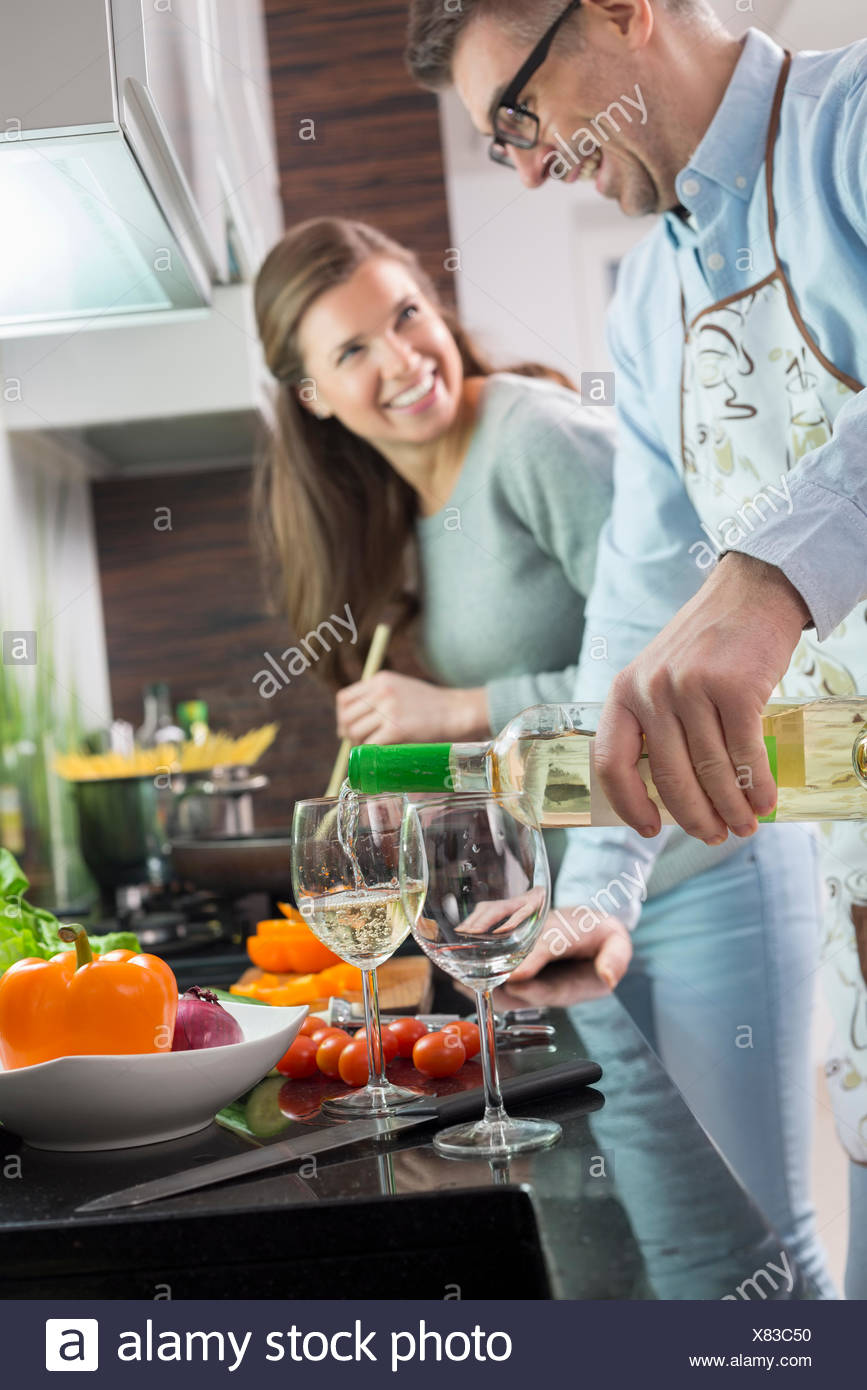 Man pouring white wine in glasses while cooking with woman at kitchen - Stock Image