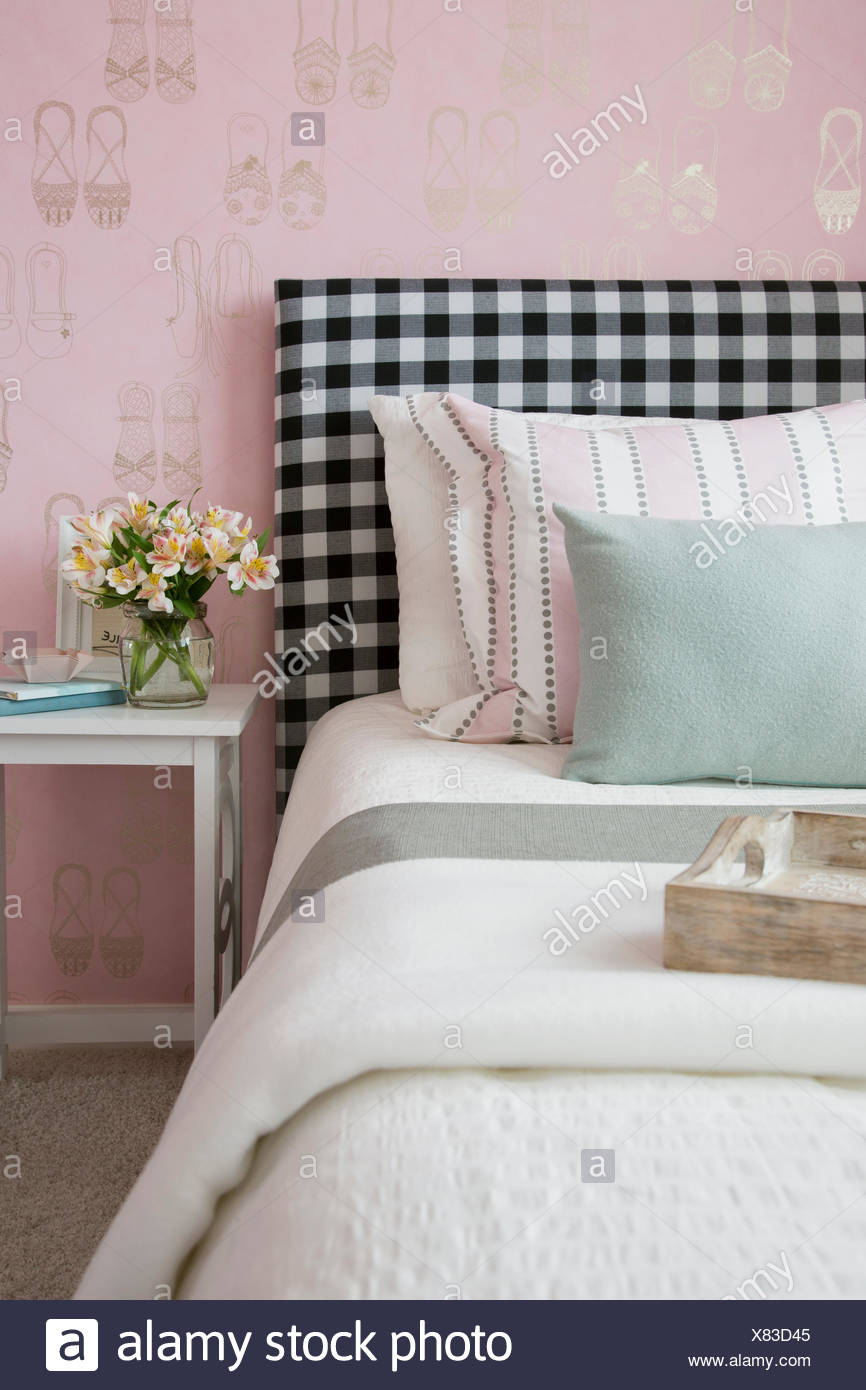 Pastel pillows on bed with gingham headboard - Stock Image