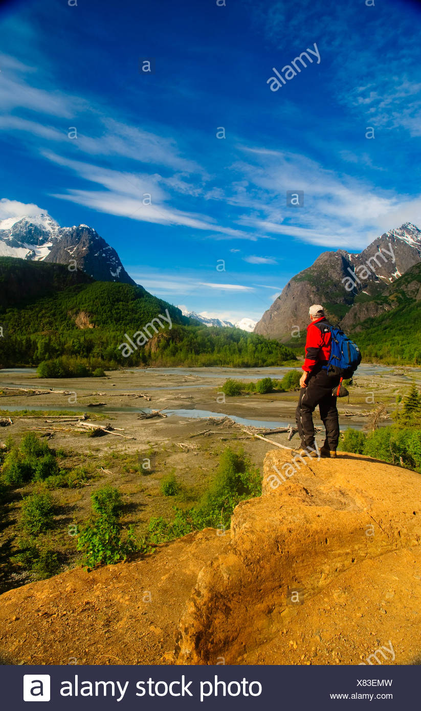 Hiker stands on a rock outcrop overlooking Eagle River, Chugach State Park, Southcentral Alaska, Summer - Stock Image