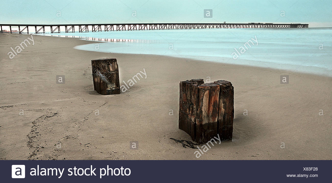 A deserted beach scene with a long jetty - Stock Image