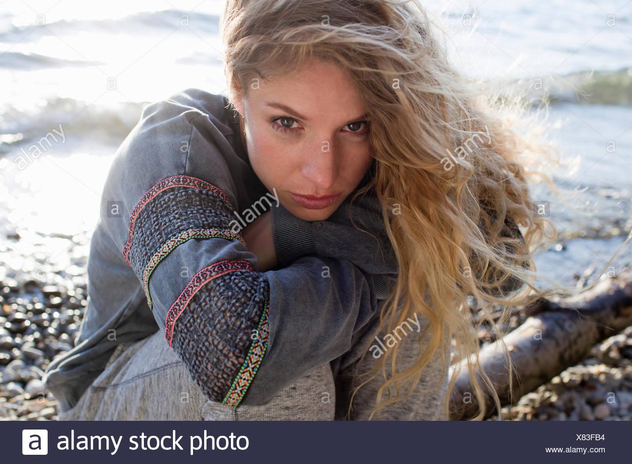 Woman sitting on windy beach - Stock Image