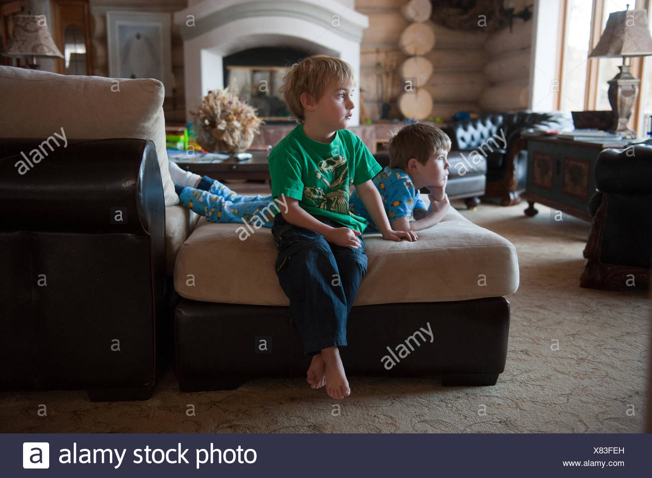 Two young boys are kept entertained by a television at their home in Denver, Colorado. - Stock Image