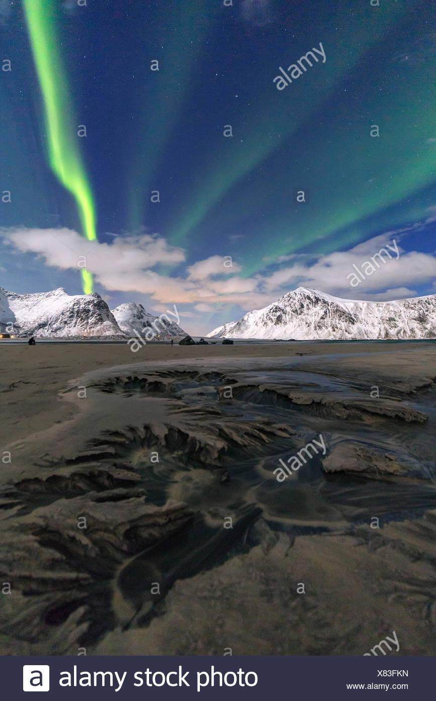 Northern Lights illuminate Skagsanden beach and the snowy peaks, Lofoten Islands Northern Norway Europe - Stock Image