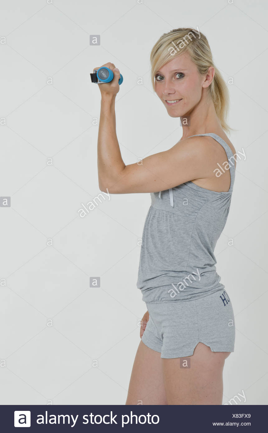 Young woman holding a small dumbbell in her right hand - Stock Image