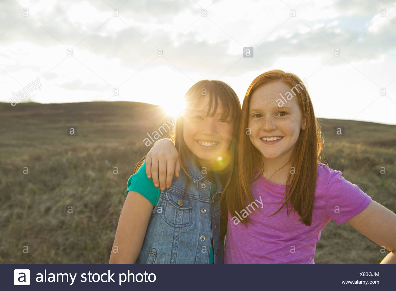 Portrait of girls with arms around each other - Stock Image