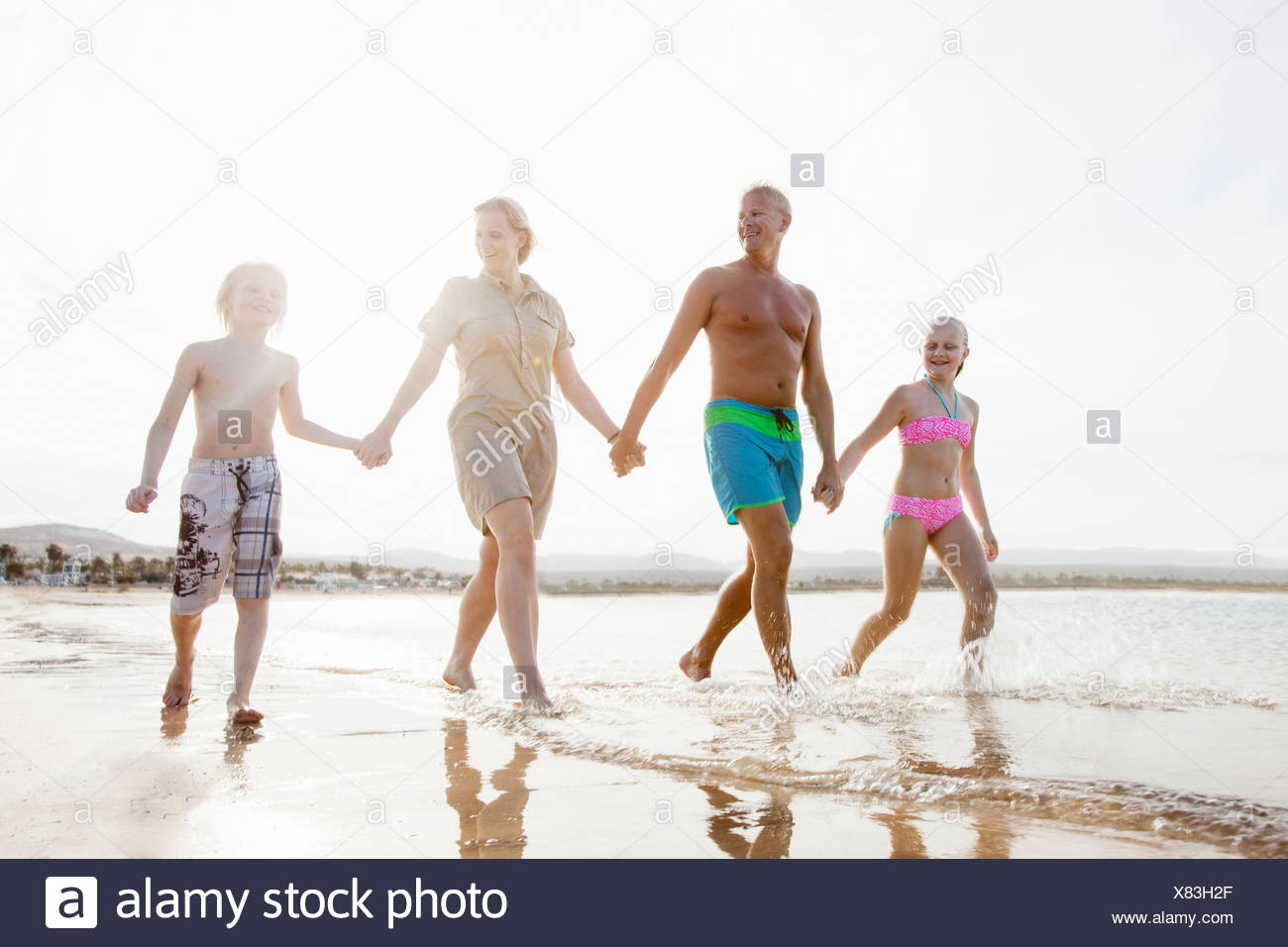 Family with two children strolling and holding hands on beach - Stock Image