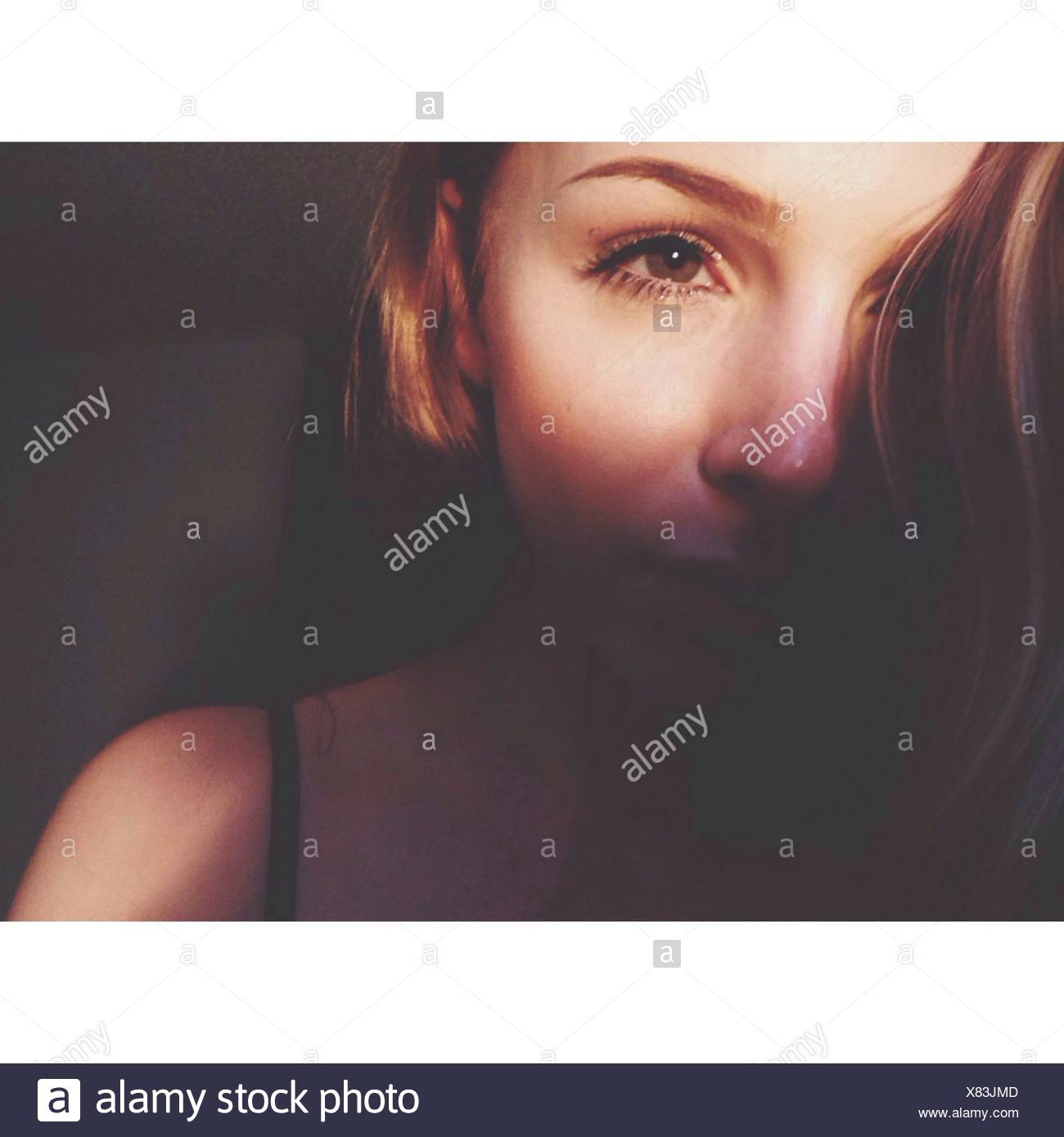 Close-Up Of A Beautiful Young Woman Over Black Background - Stock Image
