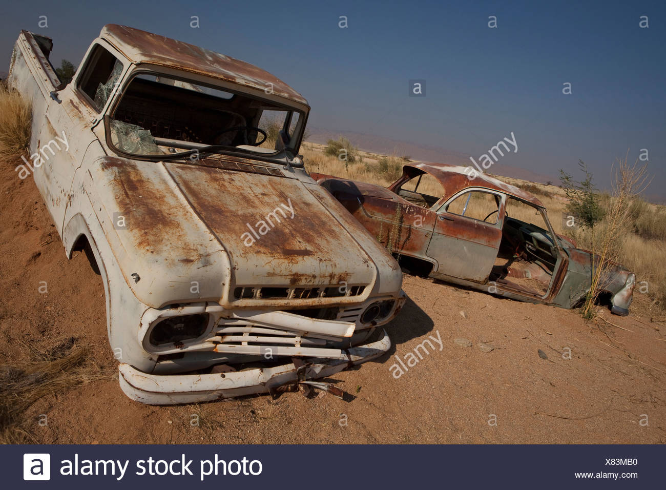 Rusting cars submerged in sand - Stock Image