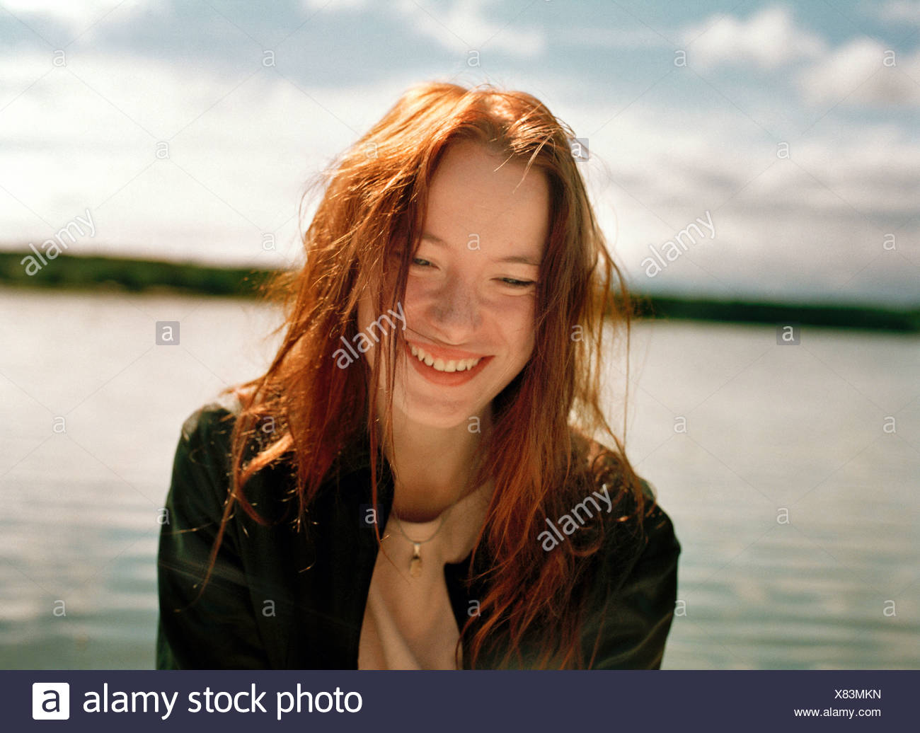 Close up of a young woman smiling near a lake Finland - Stock Image