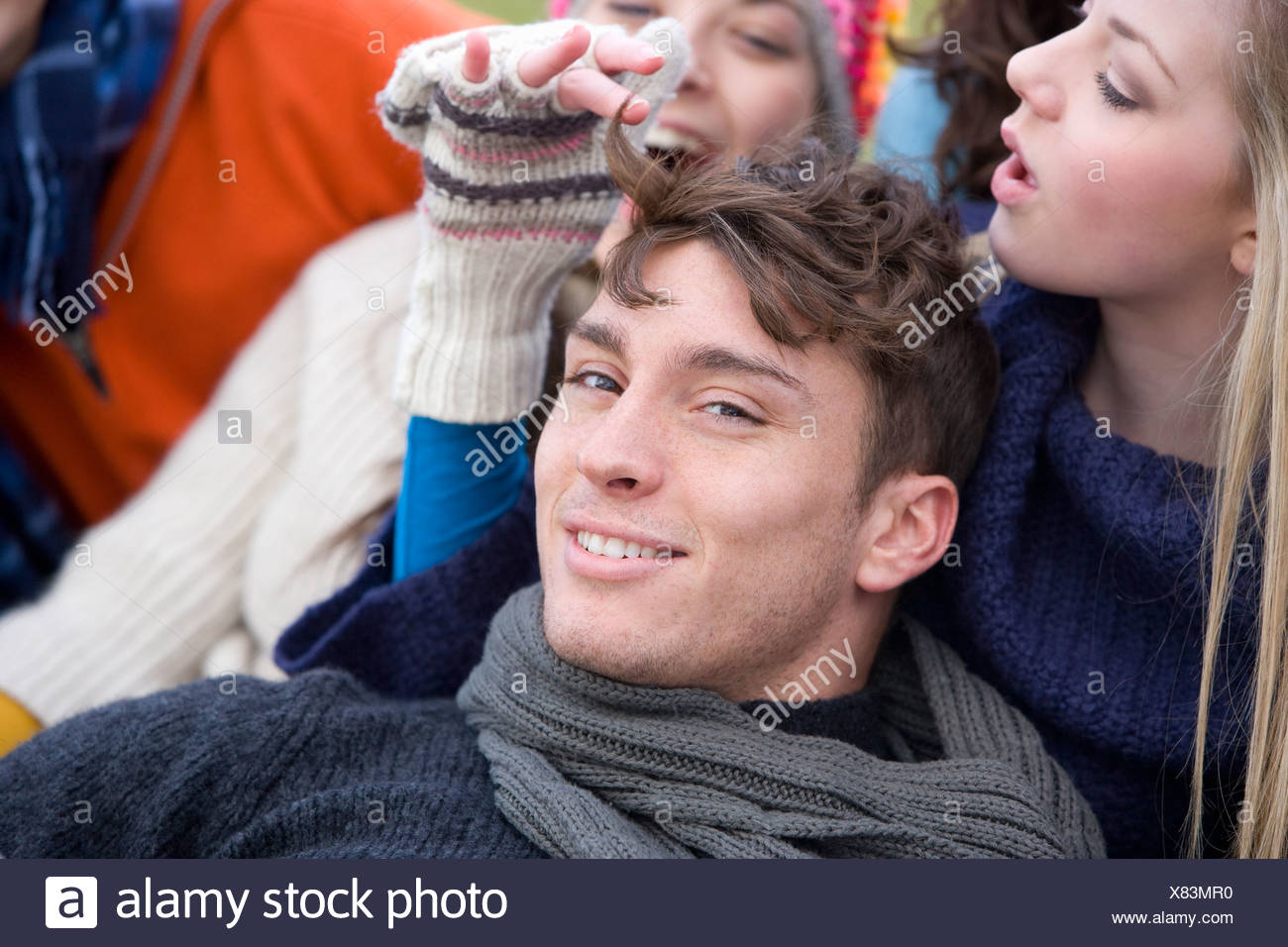 Teenage girl playing with young man's hair - Stock Image