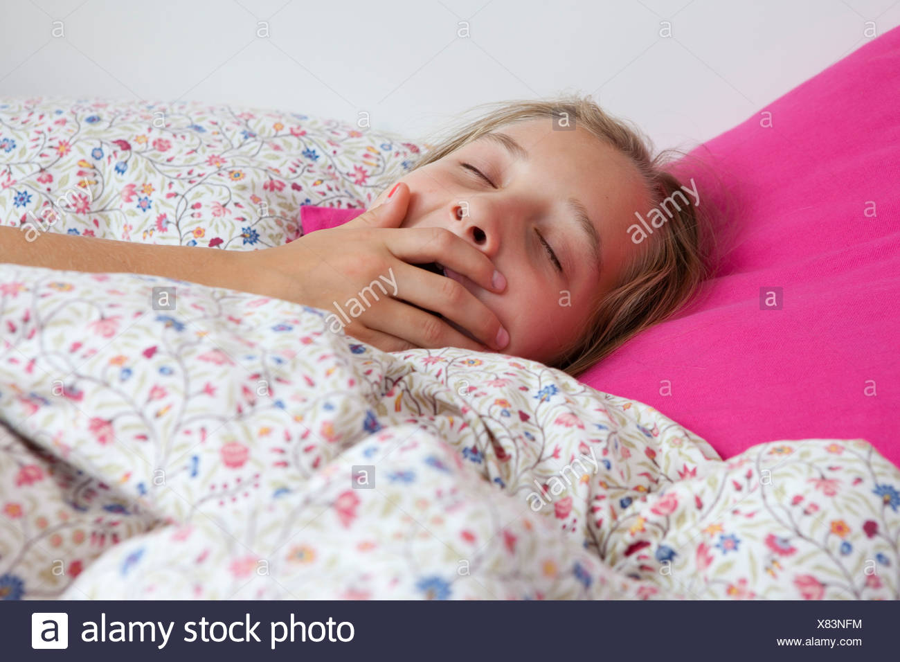 Close up of girl yawning in bed Stock Photo