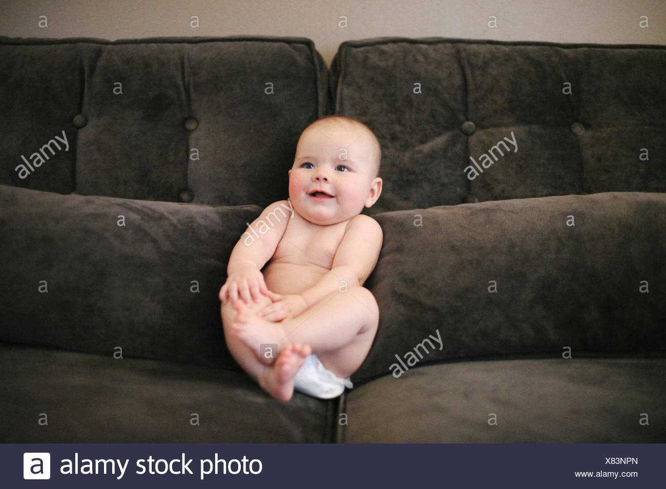 A baby sitting propped up on a sofa wearing a diaper. - Stock Image