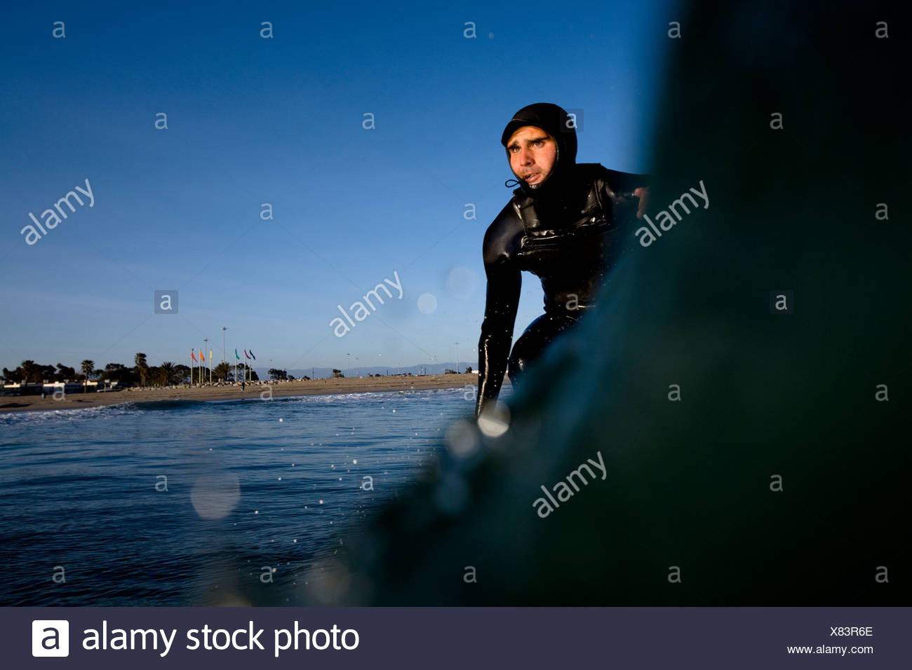 A surfer wearing a hood pumps down the line in Port Hueneme, California. - Stock Image