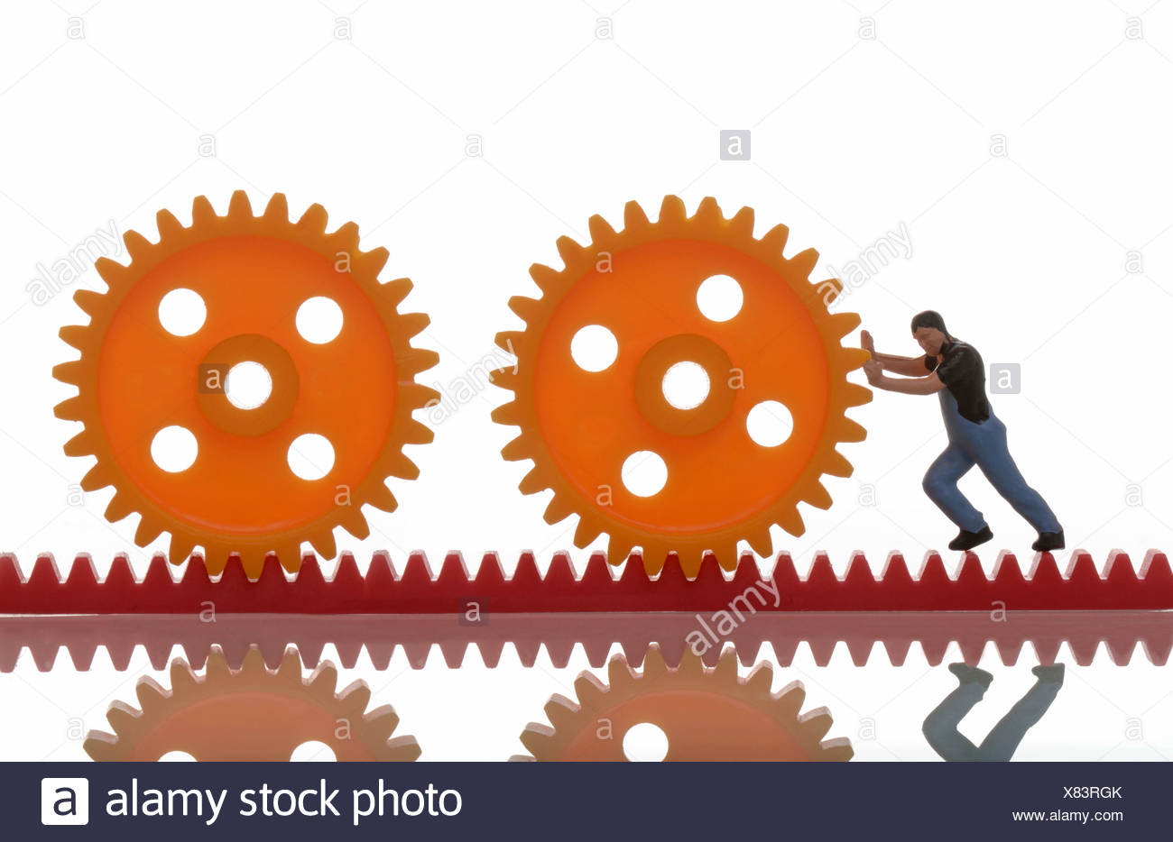 Small figurine of a workman pushing cog wheels together, symbolic image - Stock Image
