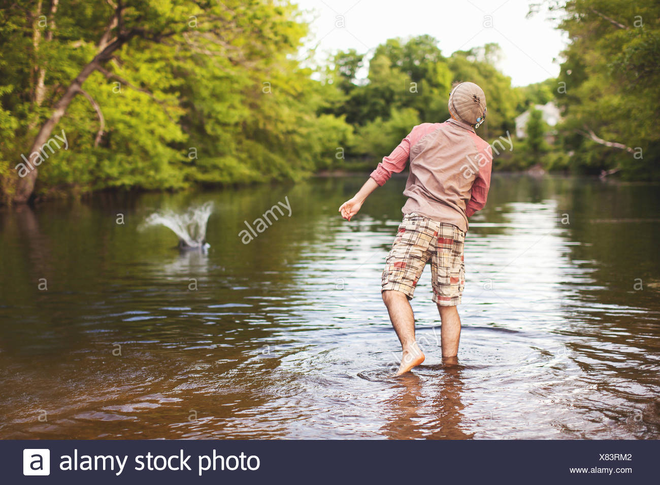Young man throwing stone into lake - Stock Image