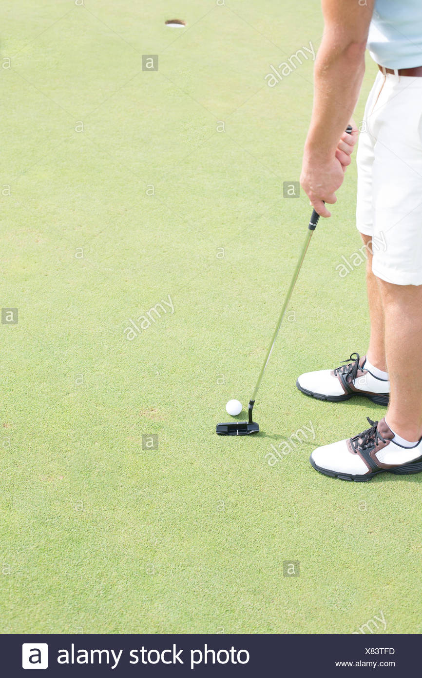Low section of mid-adult man playing golf - Stock Image