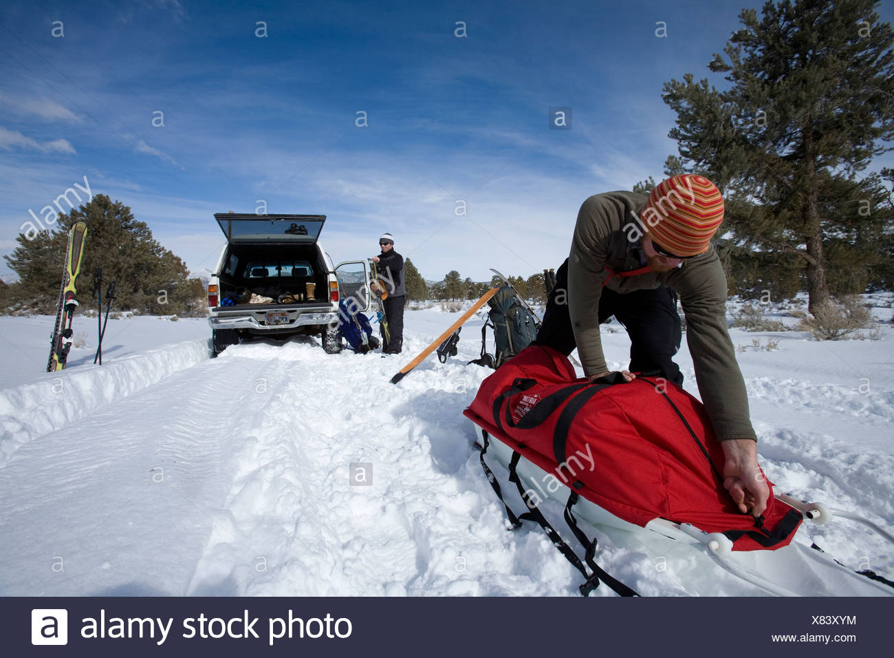 Low angle perspective of a skier zipping up his gear sled while another skier gets ready for hike into a backcountry cabin. - Stock Image
