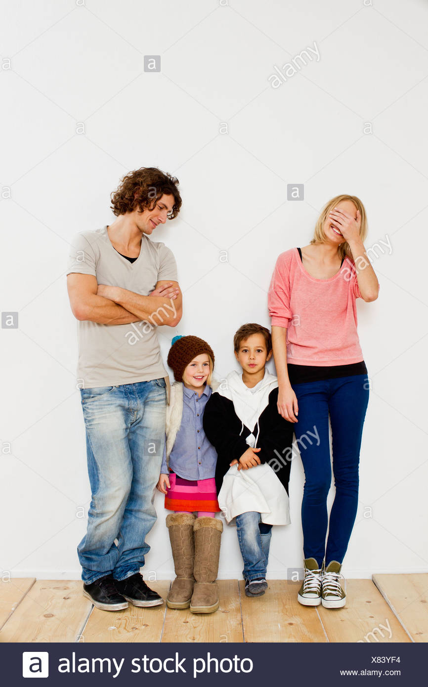 Studio shot of couple with son and daughter in oversize clothes - Stock Image