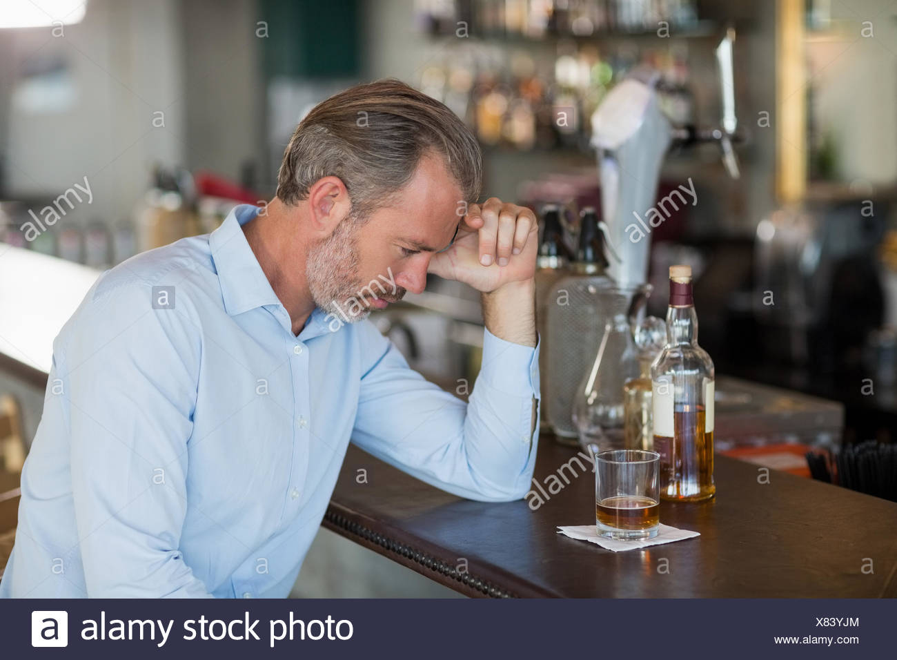 Tired man leaning his elbow on the counter - Stock Image