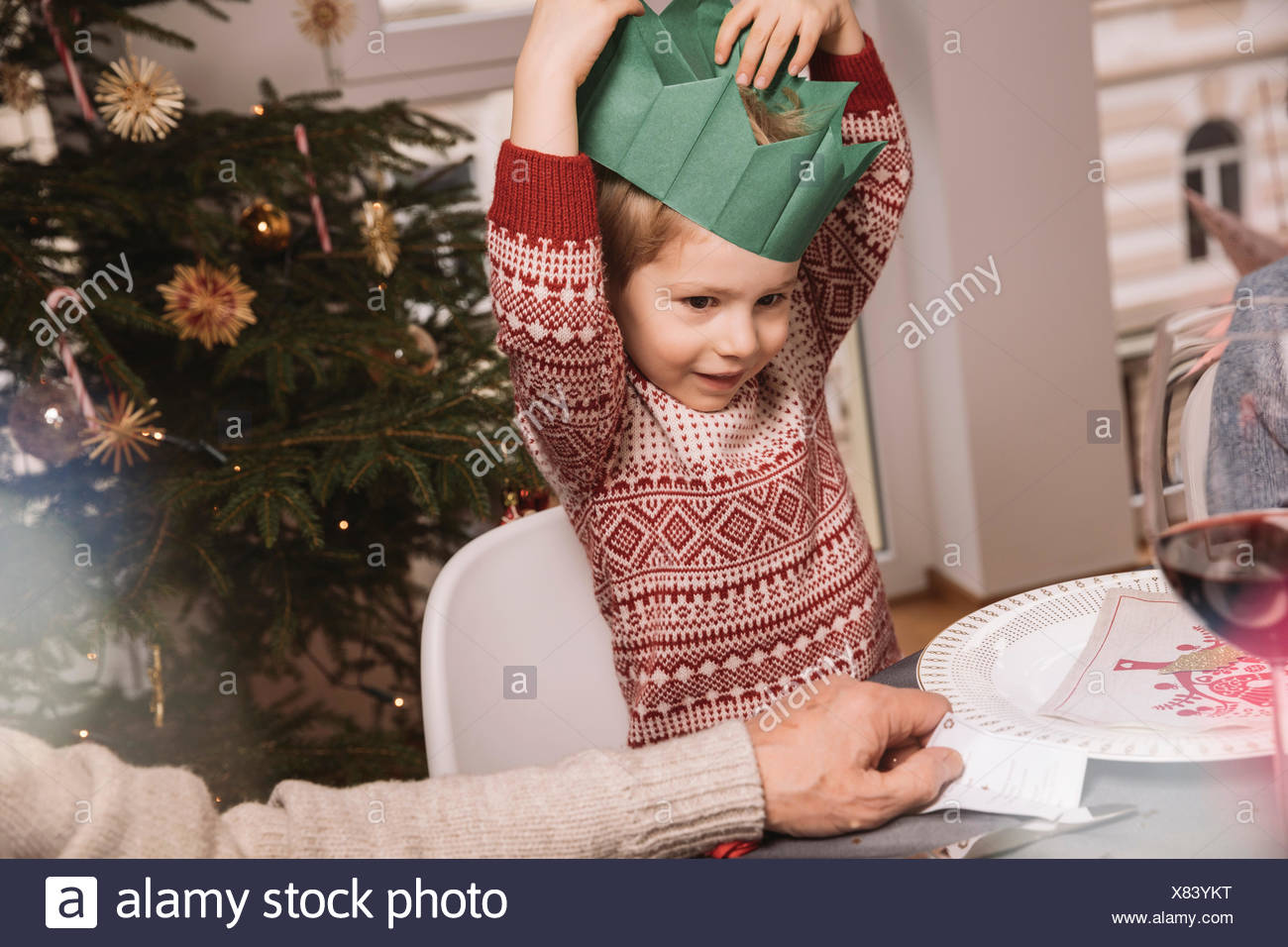A Crown For Christmas.Boy Putting On His Paper Crown For Christmas Stock Photo