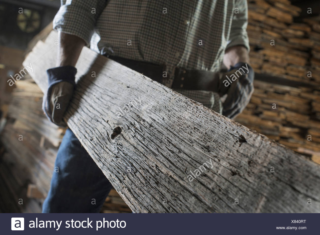 A heap of recycled reclaimed timber planks of wood Environment A man carrying a large plank of mature weathered wood - Stock Image