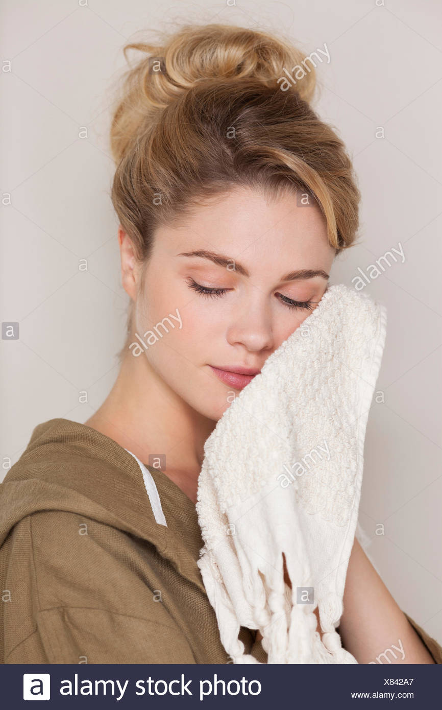 Beautiful woman cleaning her face with towel - Stock Image