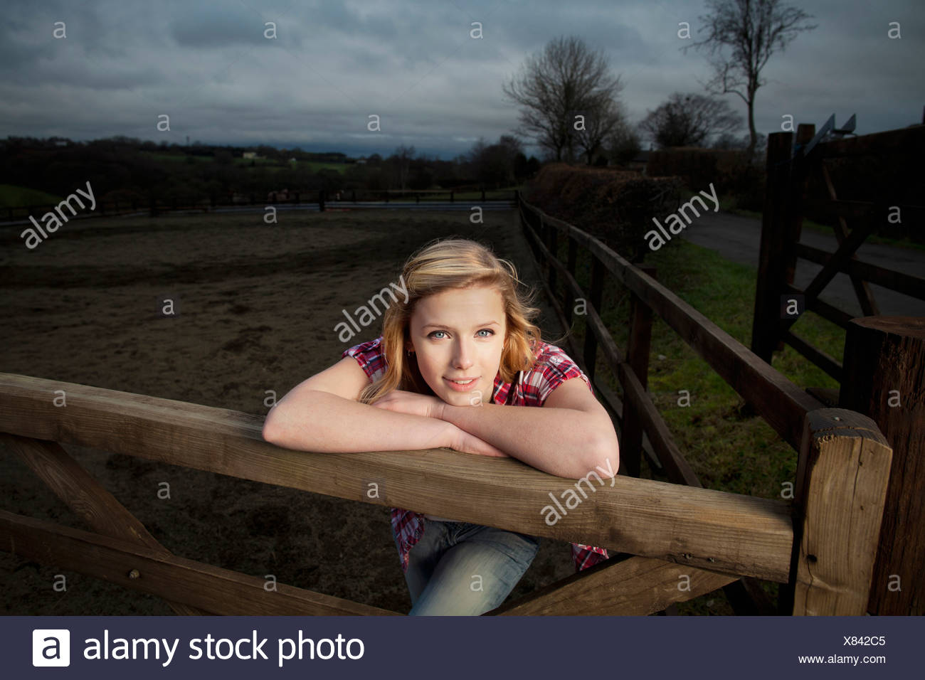 Teenage girl leaning on wooden fence - Stock Image