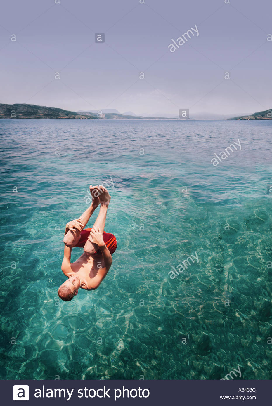 A young man somersaulting into the sea Stock Photo