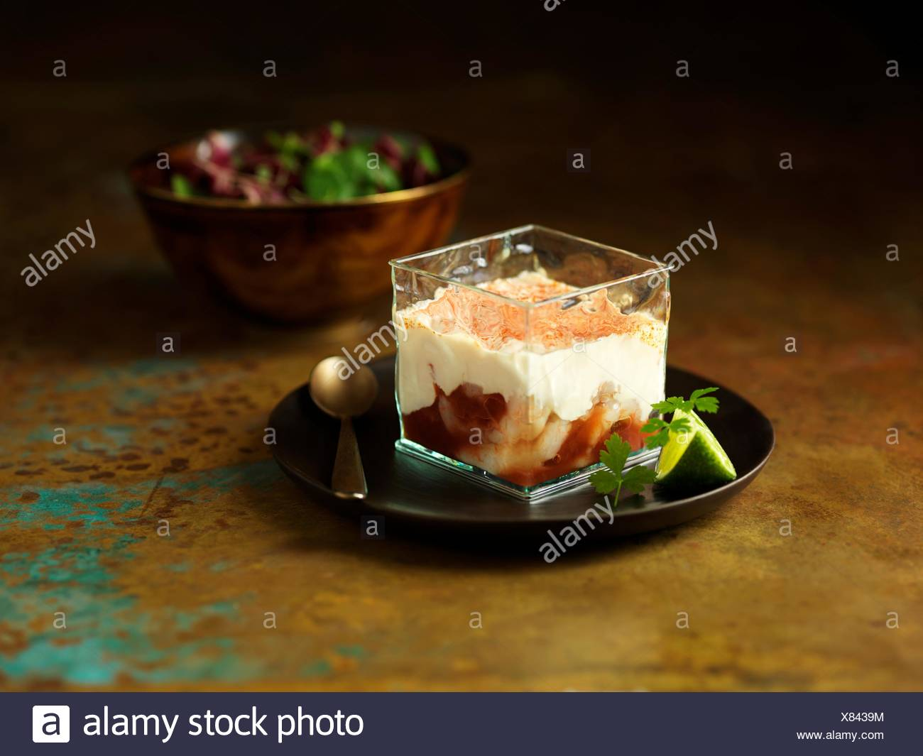 Still life of bloody mary prawn cocktail appetiser with lime, coriander and bowl of mixed salad - Stock Image