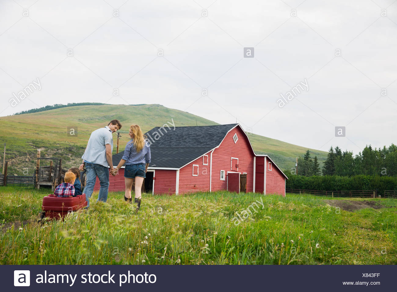 Parents pulling children in wagon outside barn Stock Photo