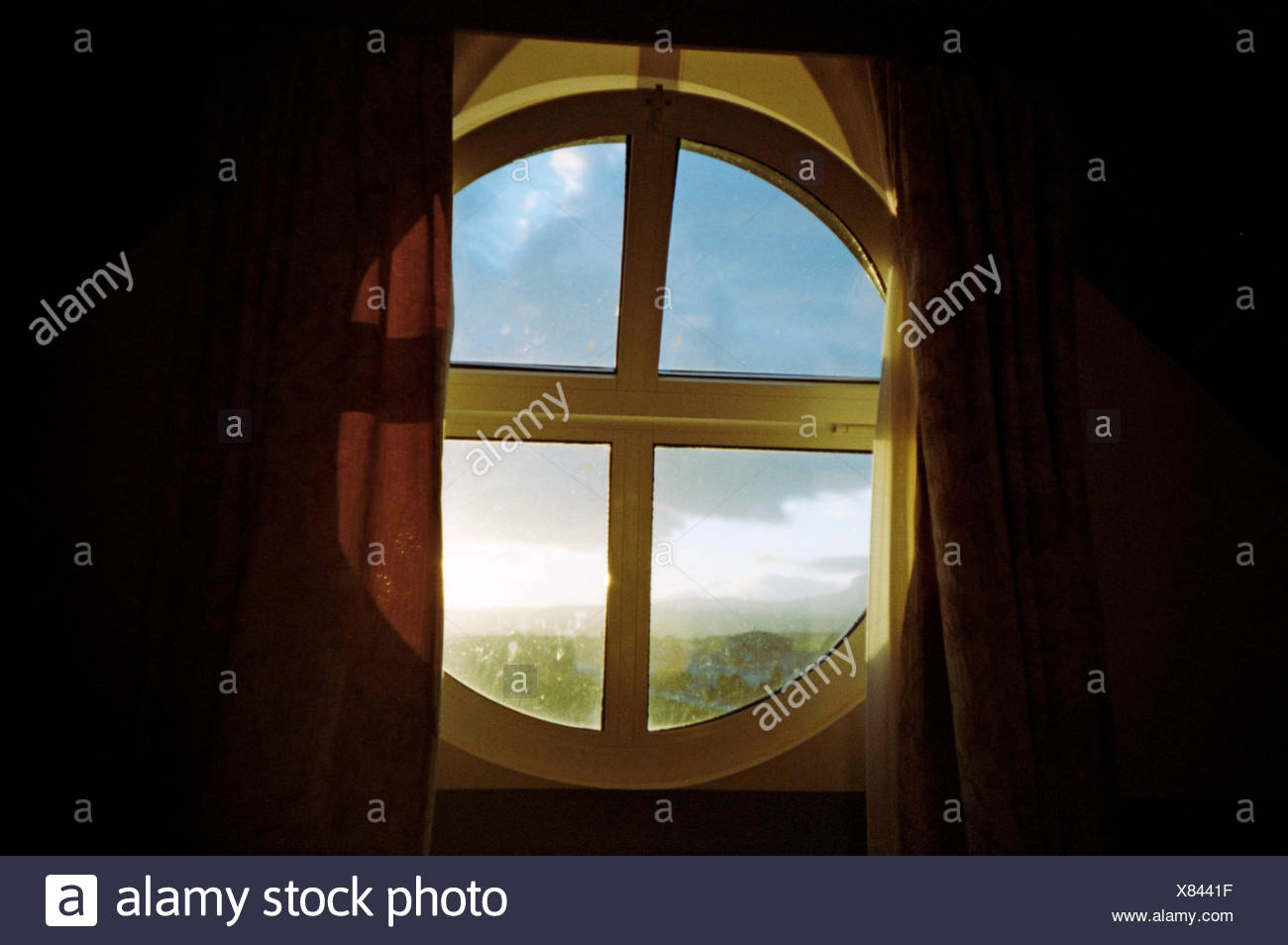 Circular Window Partially Covered With Curtain - Stock Image