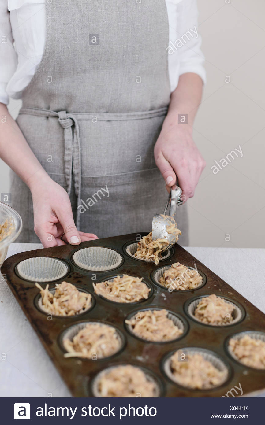 A woman is photographed from the front view as she distirbutes muffin batter into the muffin tin. Stock Photo