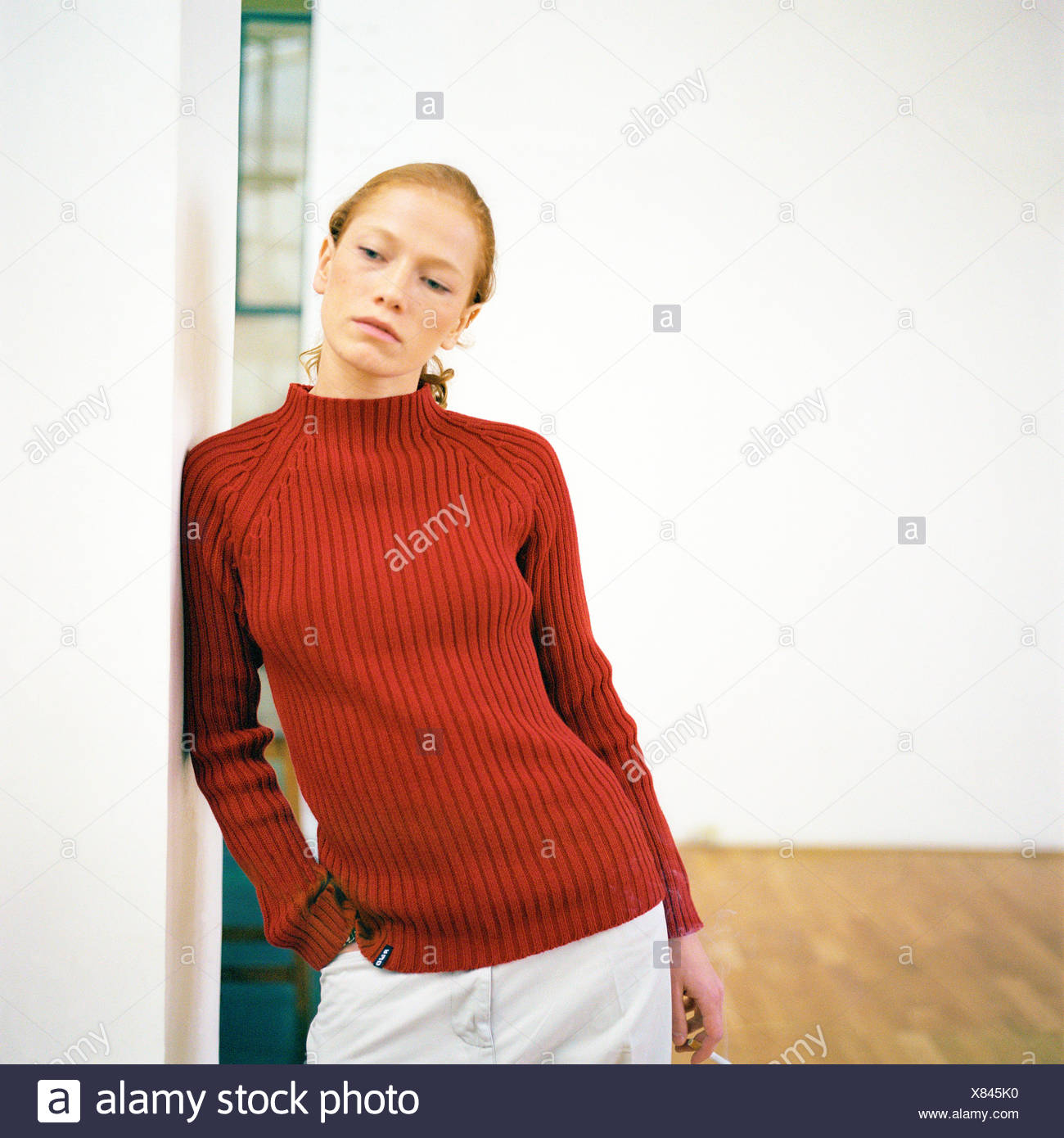 Young woman leaning against wall - Stock Image