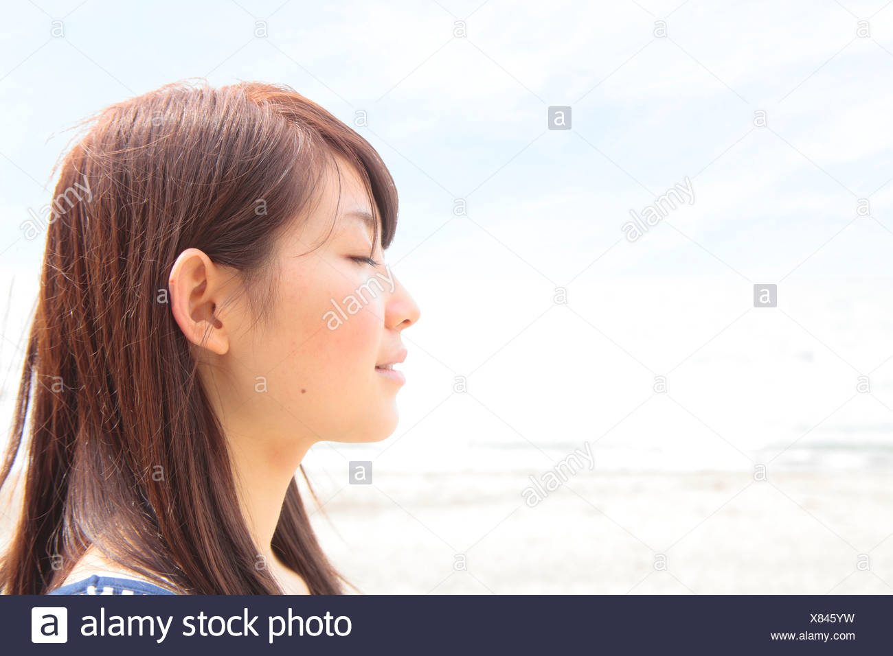 Profile of young woman with eyes closed - Stock Image