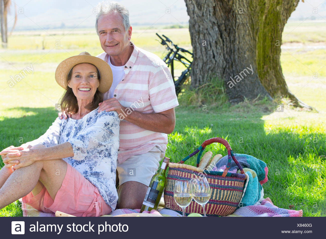 Senior couple sitting on picnic blanket - Stock Image
