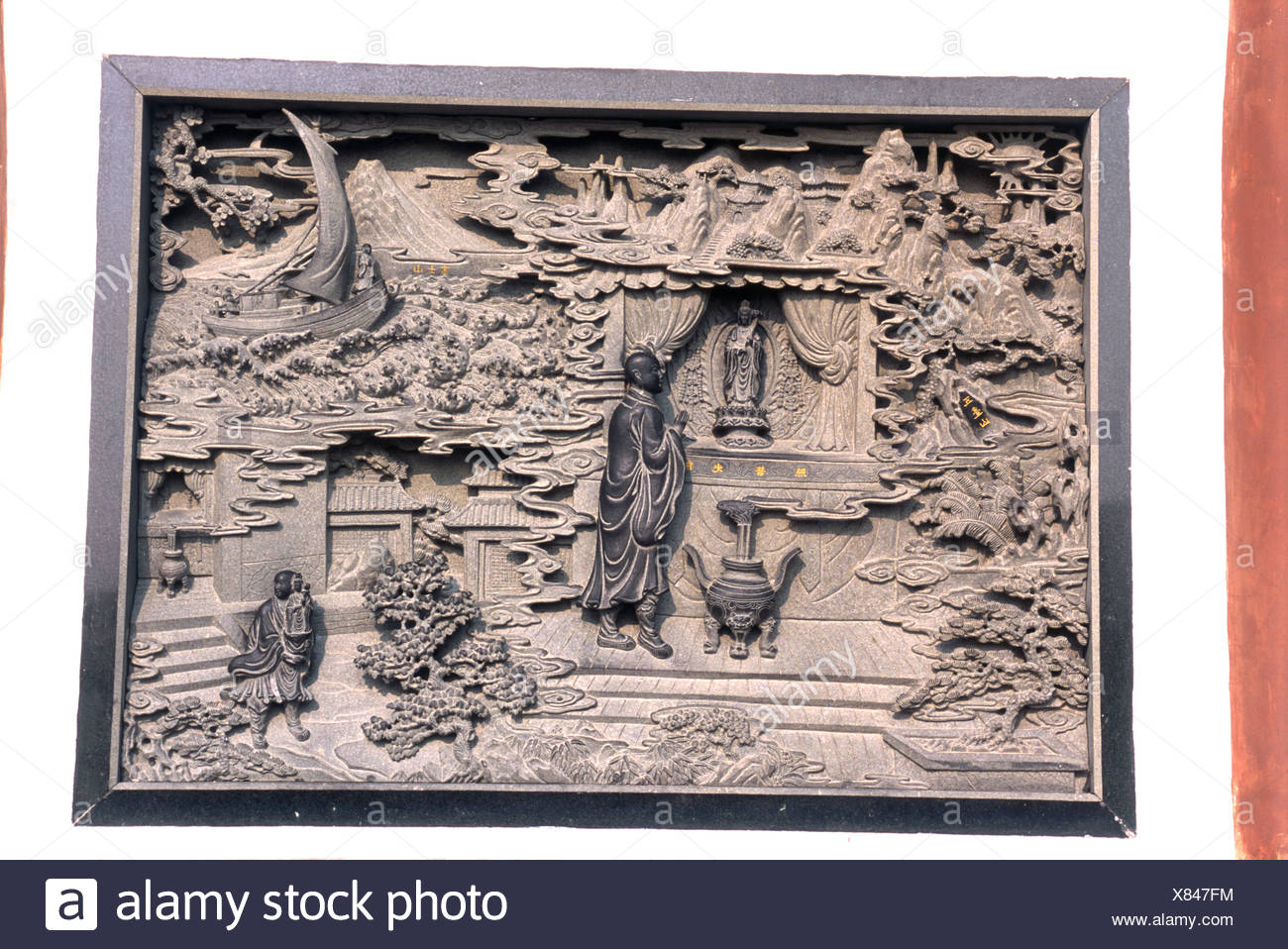 China, Zhejiang, Putuo Shan, intricately carved stonework frieze depicting Hui'e sailing in violent storm - Stock Image