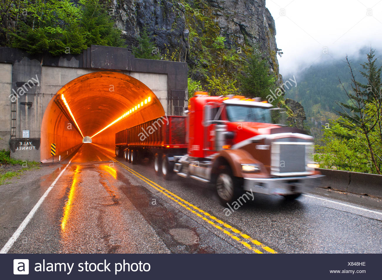 Sodium vapor lights used to illuminate a tunnel. - Stock Image