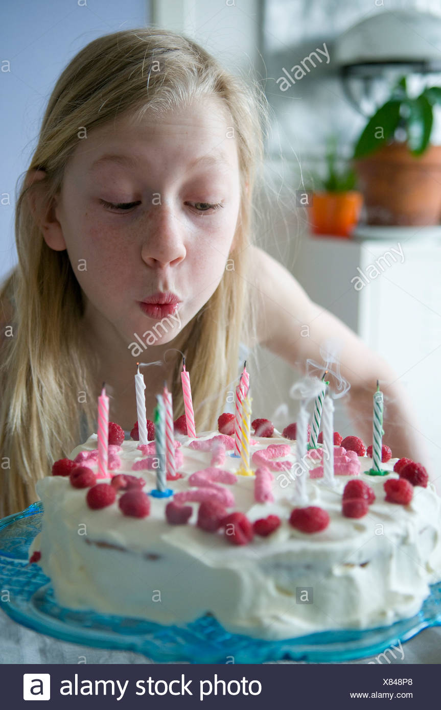 Close Up Of A Young Blond Girl Blowing Out Candles On Strawberry Cake Her 12th Birthday