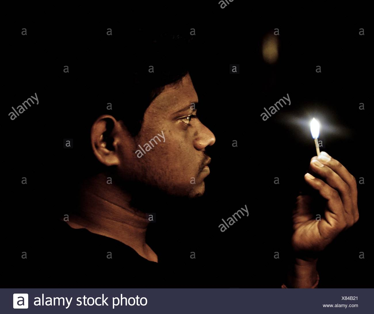 Young Man Holding Burning Matchstick At Night - Stock Image