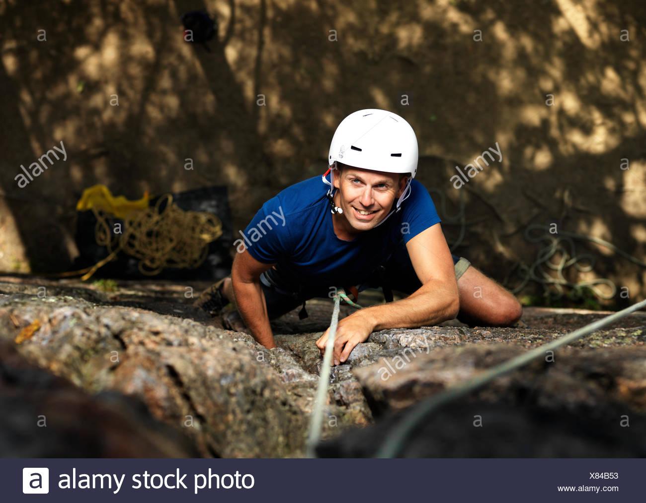 Sweden, Ostergotland, Agelsjon, Smiling man climbing rock - Stock Image