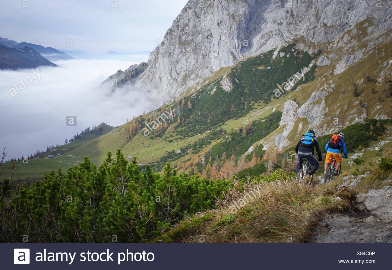Austria, Salzburg, Two mountain bike riders descending into valley - Stock Image