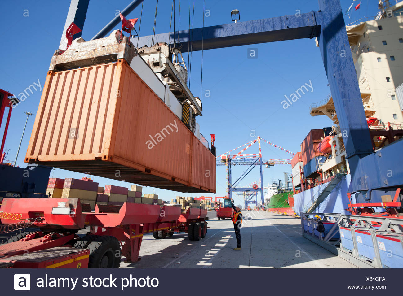 Crane unloading container ship at commercial dock - Stock Image