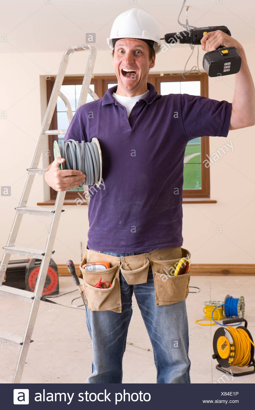 Electrician holding drill to head and making a face - Stock Image