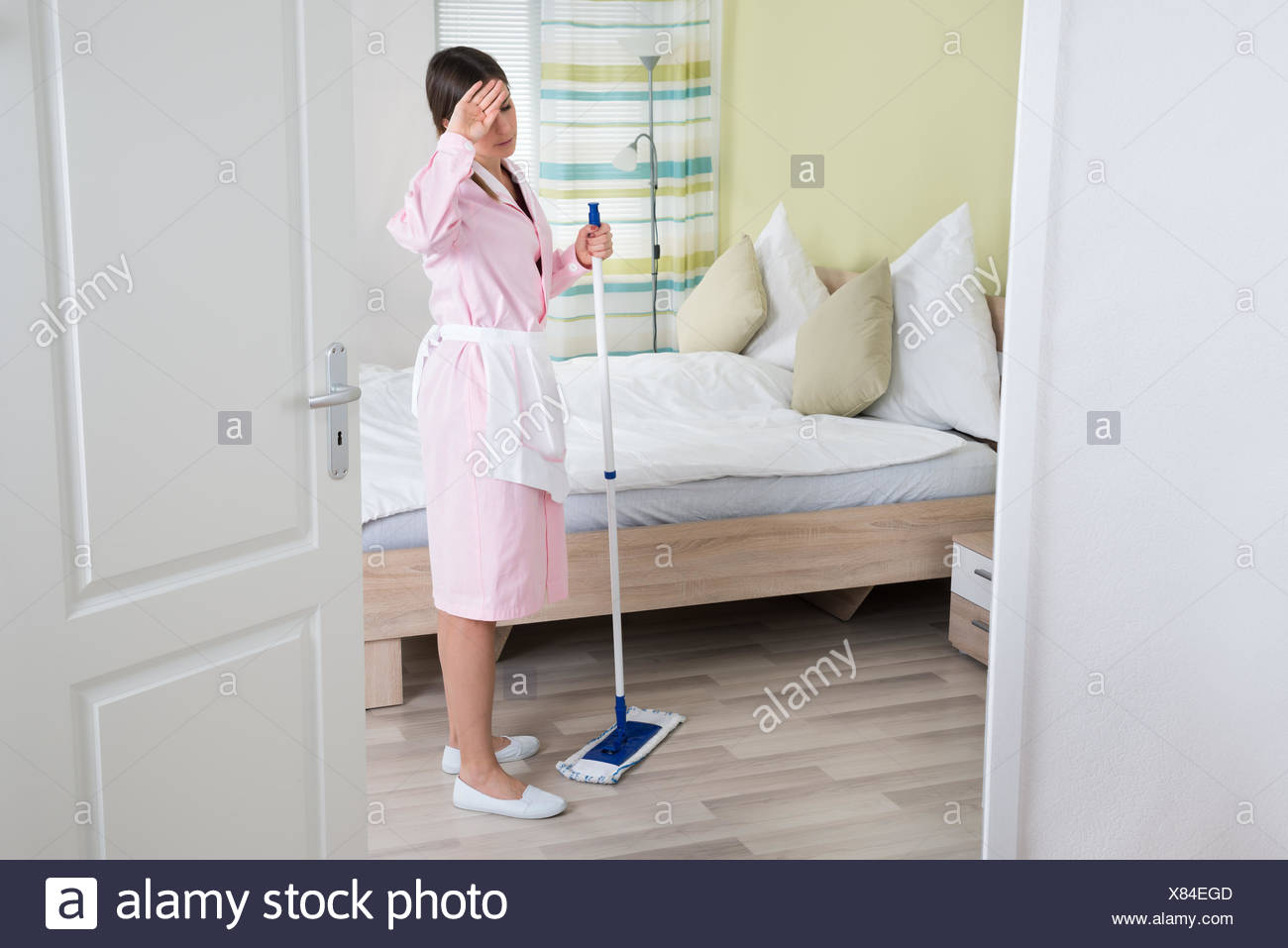 Exhausted Young Housekeeper With Mop - Stock Image