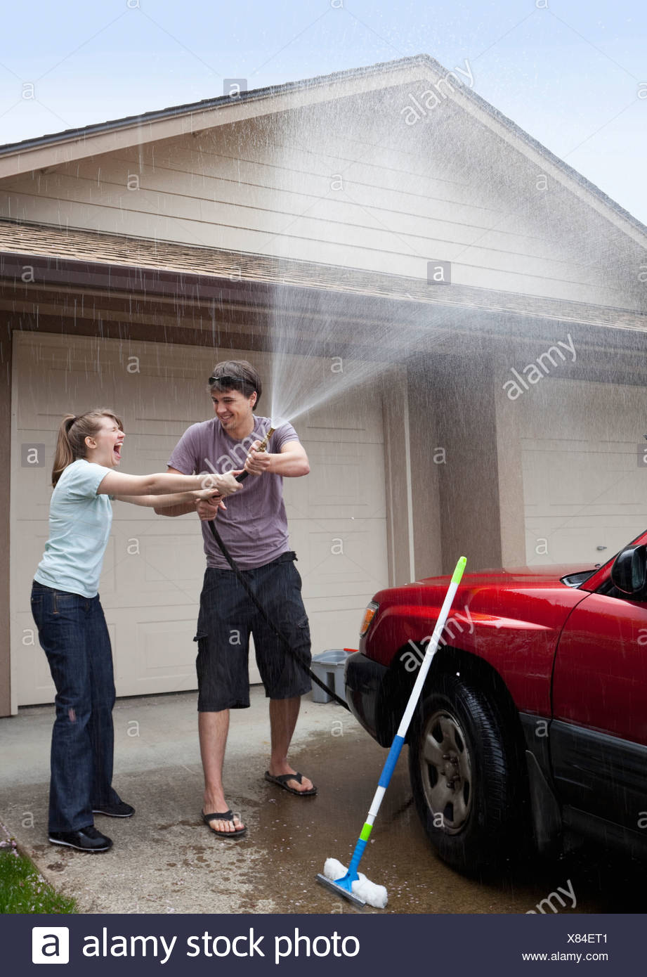 USA, Oregon, Ashland, young couple washing car in front of garage - Stock Image