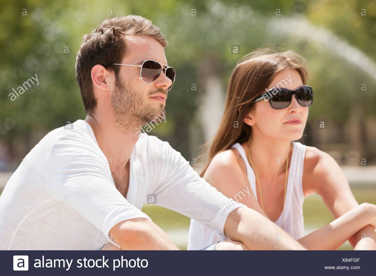 Couple sitting in a garden, Bassin octogonal, Jardin des Tuileries, Paris, Ile-de-France, France - Stock Image