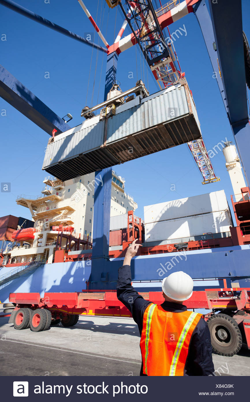Worker guiding crane with cargo container at commercial dock - Stock Image