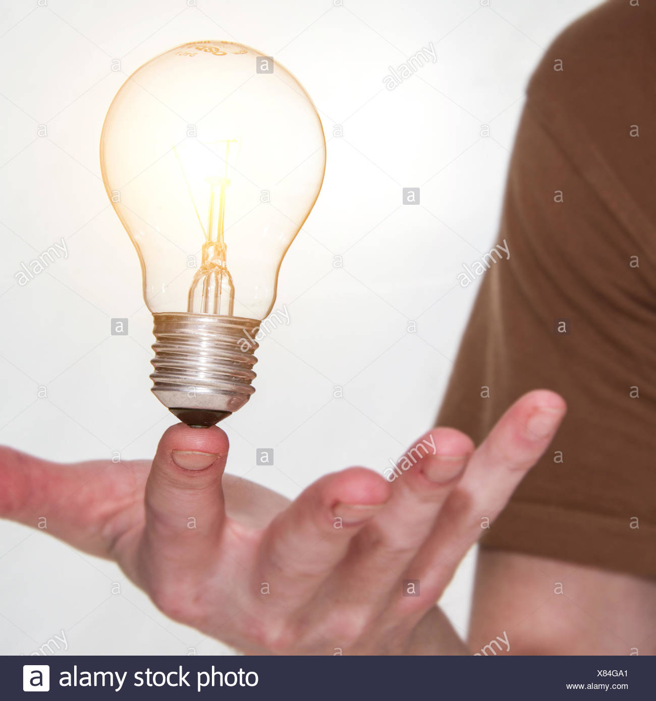 Man holding a lightbulb on his finger - Stock Image