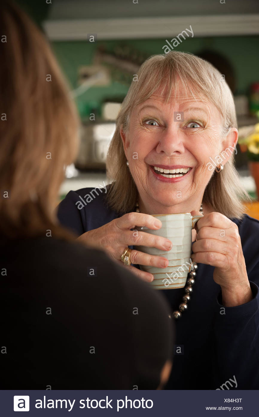 woman talk speaking speaks spoken speak talking chat nattering kitchen cuisine Stock Photo
