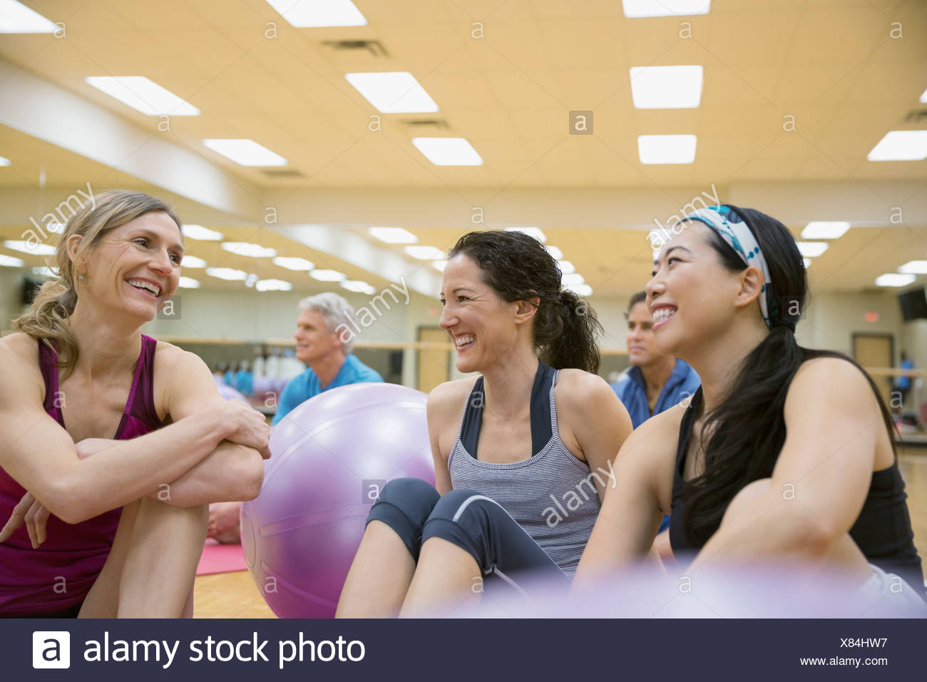 Smiling women talking in exercise class - Stock Image